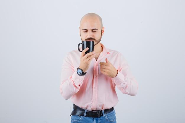 Młody mężczyzna trzyma kubek, pachnąc w różowej koszuli, dżinsach, widok z przodu.