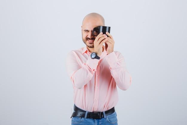 Młody mężczyzna trzyma kubek patrząc przez jego uchwyt w różowej koszuli, dżinsach, widok z przodu.
