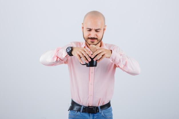 Młody mężczyzna trzyma kubek pełen gorącej herbaty w różowej koszuli, dżinsach, widok z przodu.