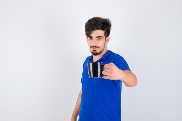 Młody mężczyzna trzyma kubek w niebieskiej koszulce i wygląda poważnie