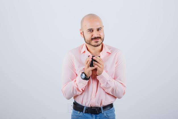 Młody mężczyzna trzyma kubek w różowej koszuli, dżinsach, widok z przodu.