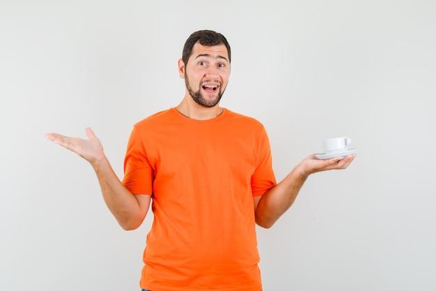 Młody mężczyzna trzyma kubek ze spodkiem w pomarańczowym t-shirt i wygląda jowialnie. przedni widok.