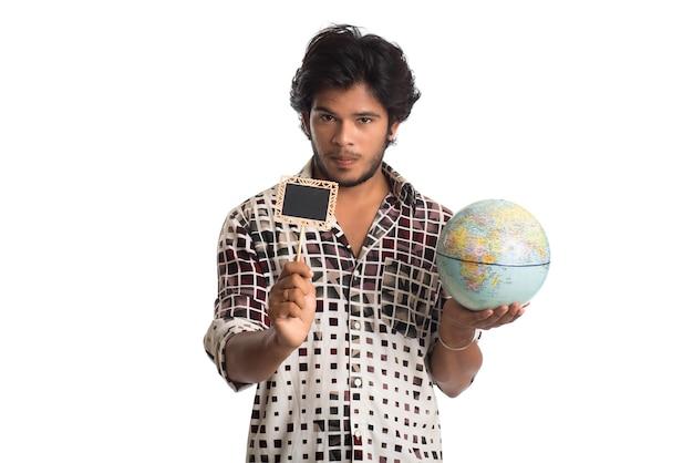 Młody mężczyzna trzyma kulę ziemską i małą deskę na białym tle.