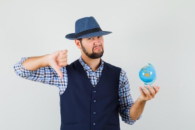 Młody mężczyzna trzyma kulę ziemską, pokazując kciuk w dół w koszuli, kamizelce, kapeluszu i patrząc niezadowolony, widok z przodu.