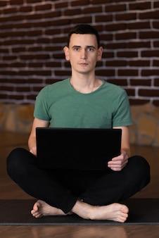 Młody mężczyzna trzyma laptop bez uśmiechu w salonie w domu
