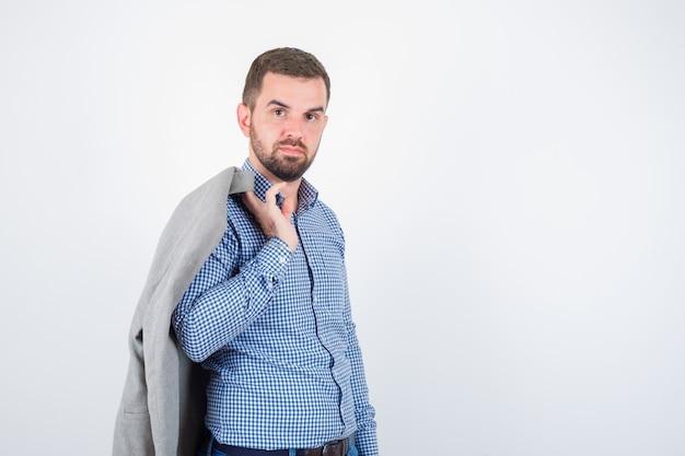 Młody mężczyzna trzyma marynarkę na ramieniu w koszuli, dżinsy, marynarkę i patrząc pewnie, z przodu.