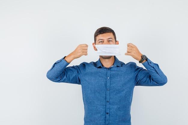 Młody mężczyzna trzyma maskę medyczną na ustach w niebieskiej koszuli, widok z przodu.