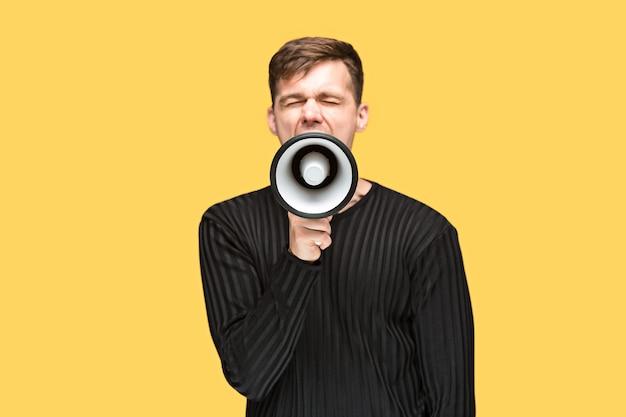 Młody mężczyzna trzyma megafon na żółtym tle studio