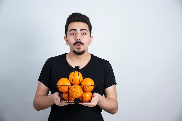 Młody mężczyzna trzyma metalowy kosz pełen pomarańczowych owoców.