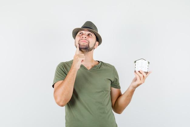 Młody mężczyzna trzyma model domu, patrząc w zielony t-shirt, kapelusz i marzycielski