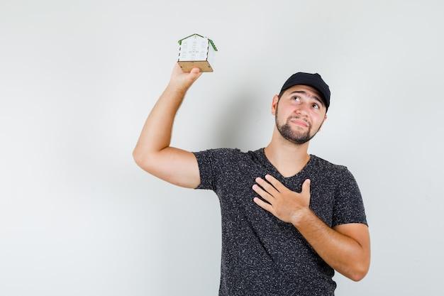 Młody mężczyzna trzyma model domu z ręką na klatce piersiowej w t-shirt i czapkę i szuka nadziei