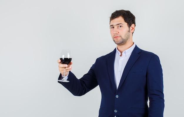 Młody mężczyzna trzyma napój alkoholowy w szkle w garniturze i wygląda pewnie. przedni widok.