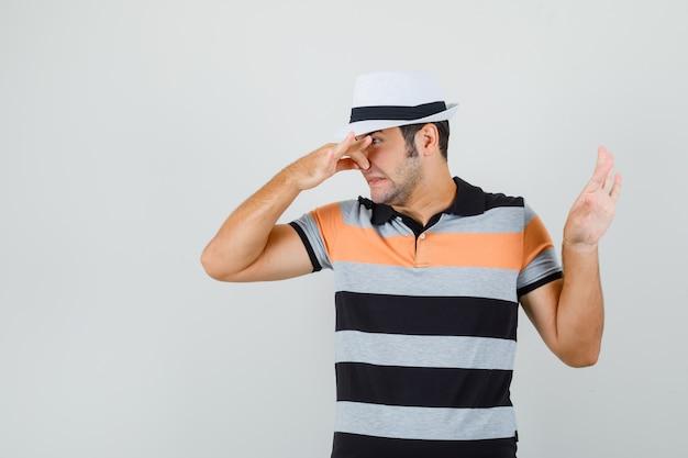 Młody mężczyzna trzyma nos, pokazując gest odrzucenia w koszulce, kapeluszu i wygląda na zniesmaczonego.