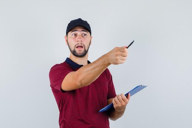 Młody mężczyzna trzyma notatnik i długopis w czerwonej koszulce, czarnej czapce i patrząc uważnie, widok z przodu.