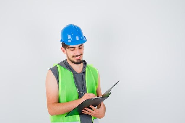 Młody mężczyzna trzyma notatnik i pisze coś na nim długopisem w mundurze budowlanym i wygląda na skupionego