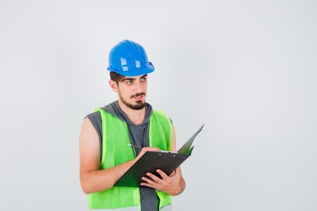 Młody mężczyzna trzyma notatnik i pisze coś na nim długopisem w mundurze budowlanym i wygląda na szczęśliwego