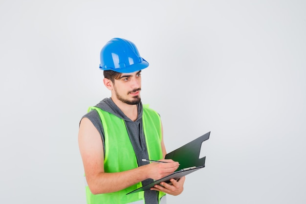 Młody mężczyzna trzyma notatnik i pisze coś na nim długopisem w mundurze budowlanym i wygląda na zamyślonego