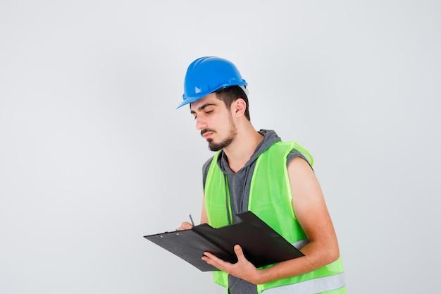 Młody mężczyzna trzyma notatnik i pisze coś na nim w mundurze budowlanym i wygląda na skupionego