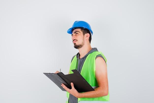 Młody mężczyzna trzyma notatnik i pisze coś na nim w mundurze budowlanym i wygląda na zamyślonego
