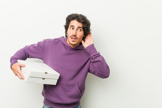 Młody mężczyzna trzyma pakiet pizzy próbuje słuchać plotek