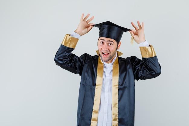 Młody mężczyzna trzyma palce na czapce w mundurze absolwenta i wygląda wesoło, widok z przodu.