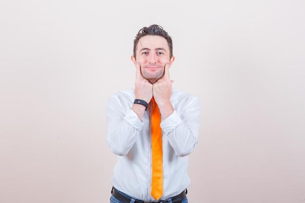 Młody mężczyzna trzyma palce na dołkach w koszuli, dżinsach i wygląda wesoło