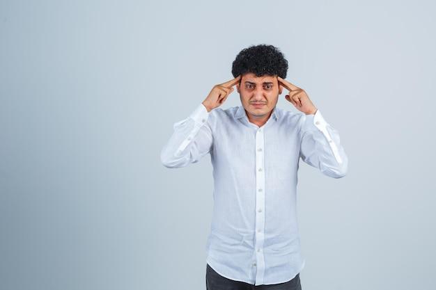 Młody mężczyzna trzyma palce na skroniach w białej koszuli i wygląda na zmęczonego, widok z przodu.