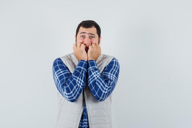 Młody mężczyzna trzyma pięści na ustach w koszuli, kurtce bez rękawów i wygląda na zmartwionego. przedni widok.