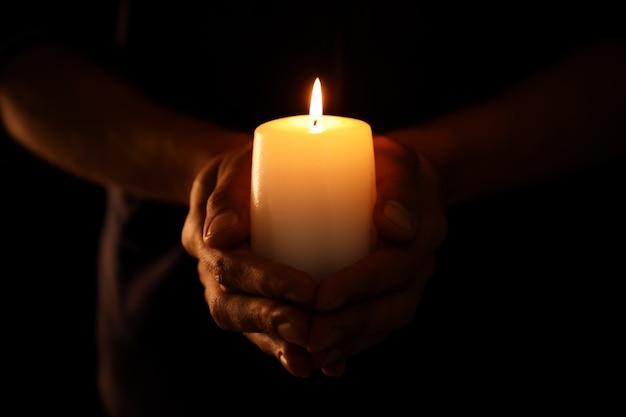 Młody mężczyzna trzyma płonącą świecę w ciemności
