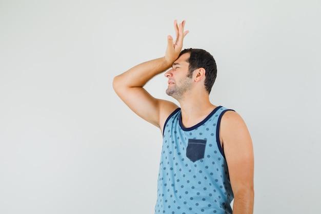 Młody mężczyzna trzyma podniesioną rękę na czole w niebieskim podkoszulku i wygląda na zmartwionego