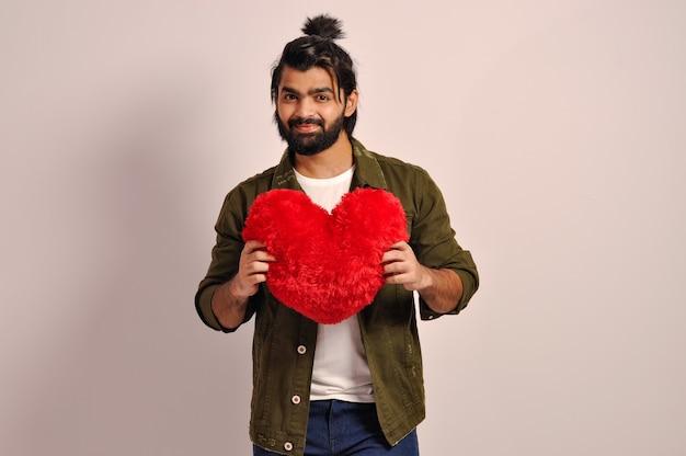 Młody mężczyzna trzyma poduszkę w kształcie czerwonego serca na walentynki