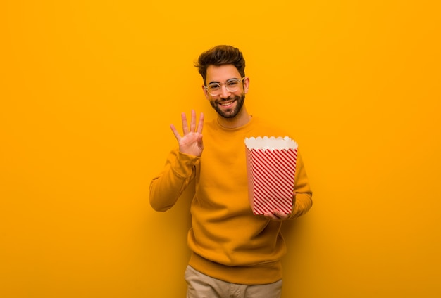 Młody mężczyzna trzyma popcorns pokazując numer cztery
