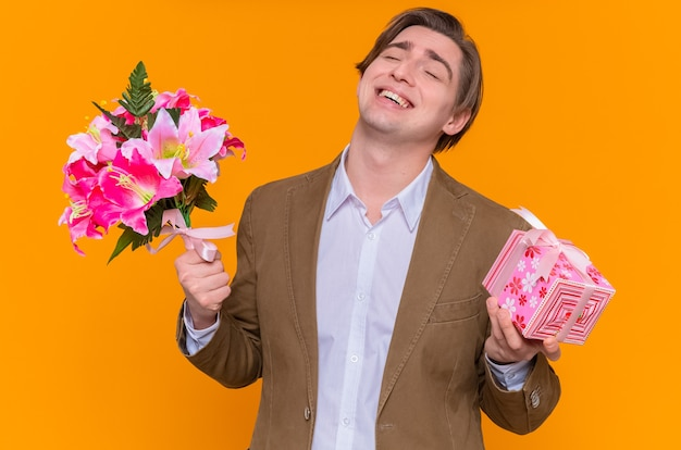 Młody mężczyzna trzyma prezent i bukiet kwiatów szczęśliwy i podekscytowany, uśmiechnięty, będzie pogratulować międzynarodowego dnia kobiet stojącego nad pomarańczową ścianą