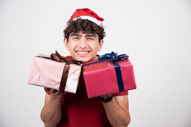 Młody mężczyzna trzyma pudełka na prezenty i uśmiechnięty.
