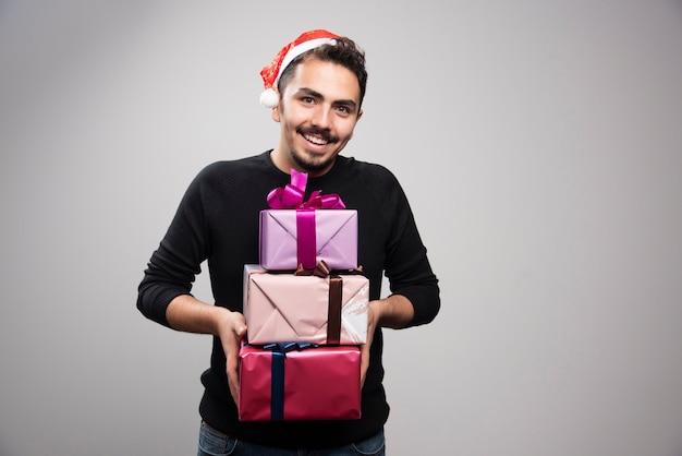Młody mężczyzna trzyma pudełka na prezenty na szarej ścianie.