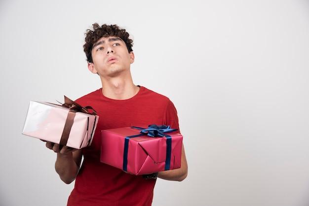 Młody mężczyzna trzyma pudełka na prezenty