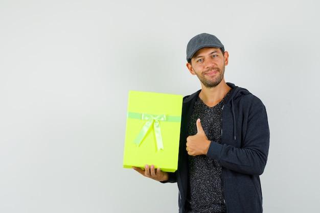 Młody mężczyzna trzyma pudełko i pokazuje kciuk w t-shirt, kurtkę, widok z przodu czapki.