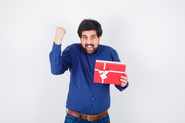 Młody mężczyzna trzyma pudełko i pokazuje zwycięzcę poza w niebieskiej koszuli i dżinsach i patrząc optymistycznie, widok z przodu.
