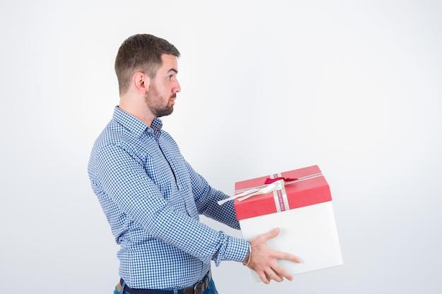 Młody mężczyzna trzyma pudełko w koszuli i wygląda zdumiony. przedni widok.