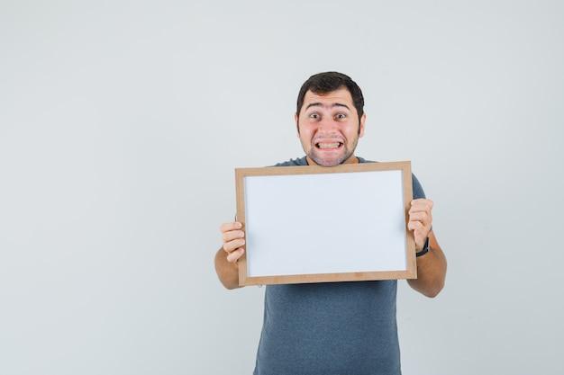 Młody mężczyzna trzyma pustą ramkę w szarej koszulce i szuka zadowolony