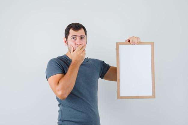 Młody mężczyzna trzyma pustą ramkę w szarej koszulce i wygląda niespokojnie