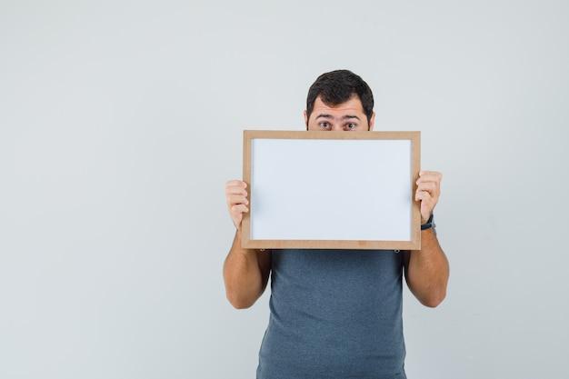Młody mężczyzna trzyma pustą ramkę w szarej koszulce i wygląda przestraszony