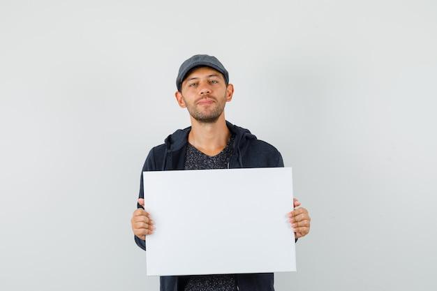 Młody mężczyzna trzyma puste płótno i uśmiecha się w t-shirt, kurtkę, widok z przodu czapki.