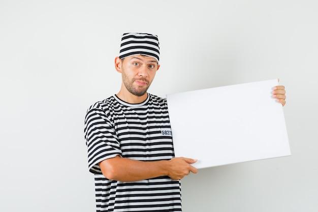 Młody mężczyzna trzyma puste płótno w kapeluszu t-shirt w paski i wygląda optymistycznie