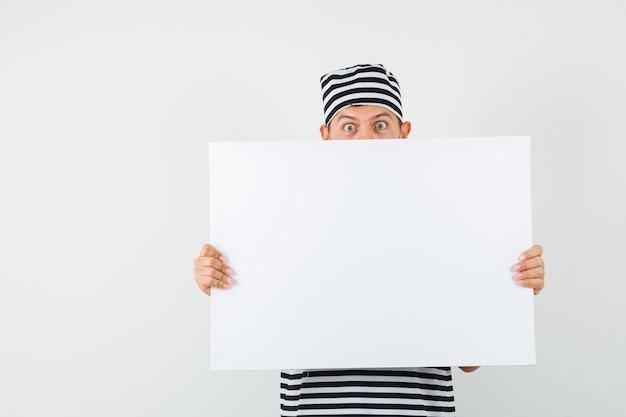 Młody mężczyzna trzyma puste płótno w kapeluszu t-shirt w paski i wygląda przestraszony