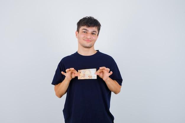 Młody mężczyzna trzyma rachunek euro w czarnej koszulce i wygląda pewnie. przedni widok.