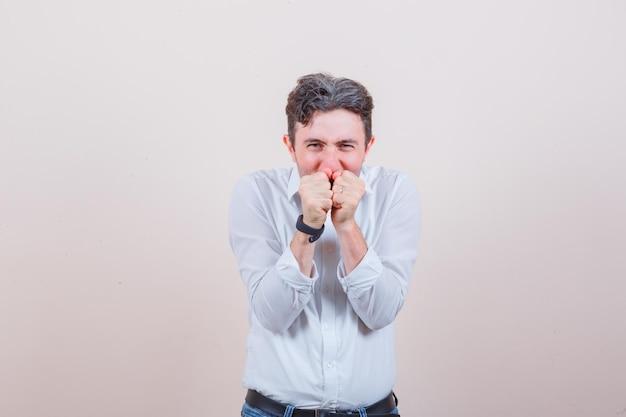 Młody mężczyzna trzyma razem pięści nad ustami w białej koszuli, dżinsach i wygląda na szczęśliwego