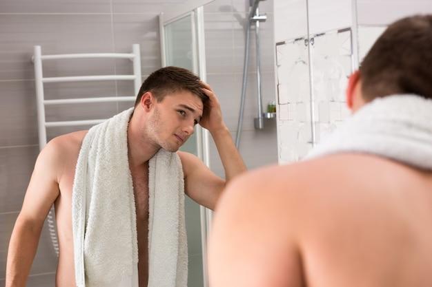 Młody mężczyzna trzyma ręcznik na ramionach po zabiegach mycia podczas oglądania lustrzanego odbicia stojącego w nowoczesnej, wyłożonej kafelkami łazience