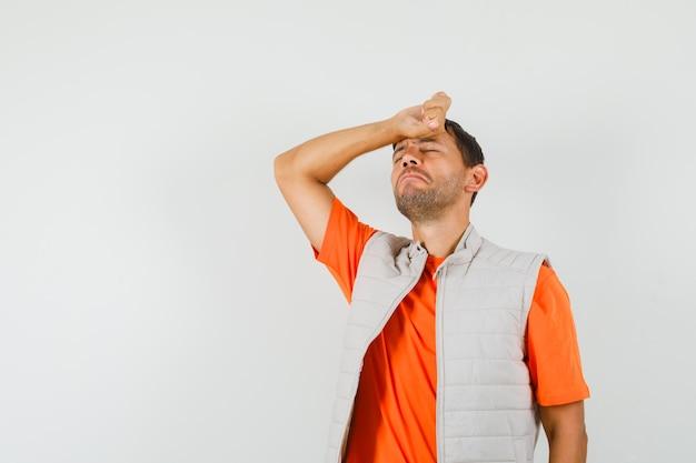 Młody mężczyzna trzyma rękę na czole w t-shirt, kurtkę i szuka wyczerpany. przedni widok.