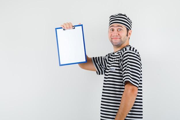 Młody mężczyzna trzyma schowek w t-shirt, kapelusz i wygląda pięknie. .